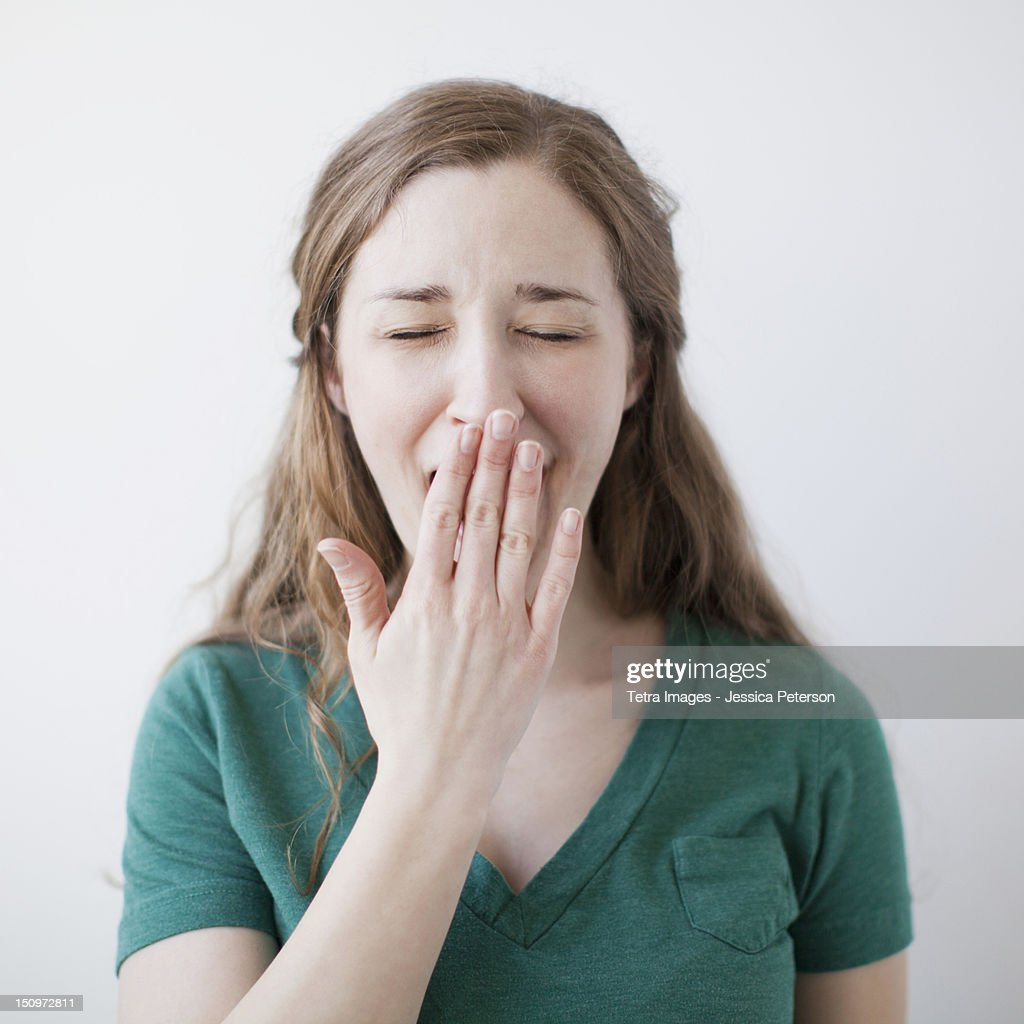 Studio shot of happy young woman yawning