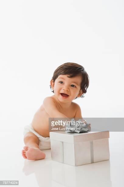 Studio shot of Hispanic baby playing with gift