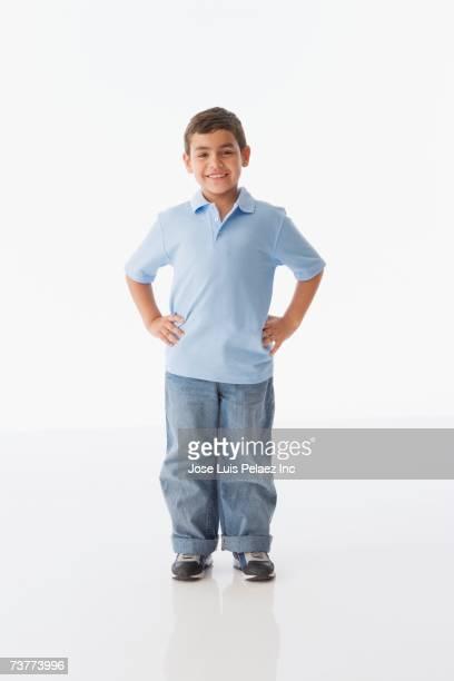 Studio shot of Hispanic boy with hands on hips