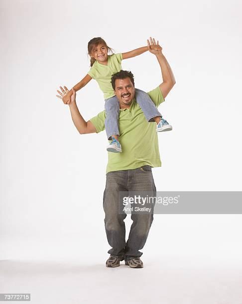 Studio shot of Hispanic father holding daughter on shoulders