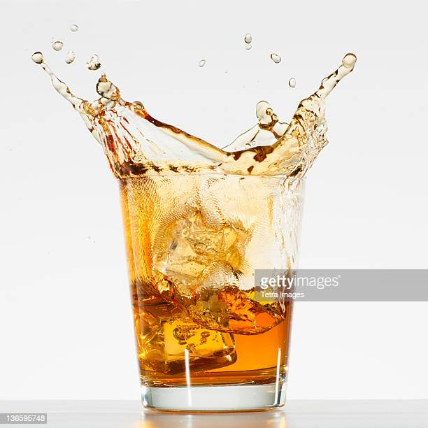 Studio shot of ice cubes splashing into glass of whiskey