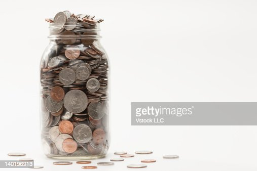 Studio shot of jar full of coins