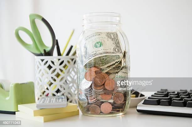 Studio Shot of jar full of money on desk