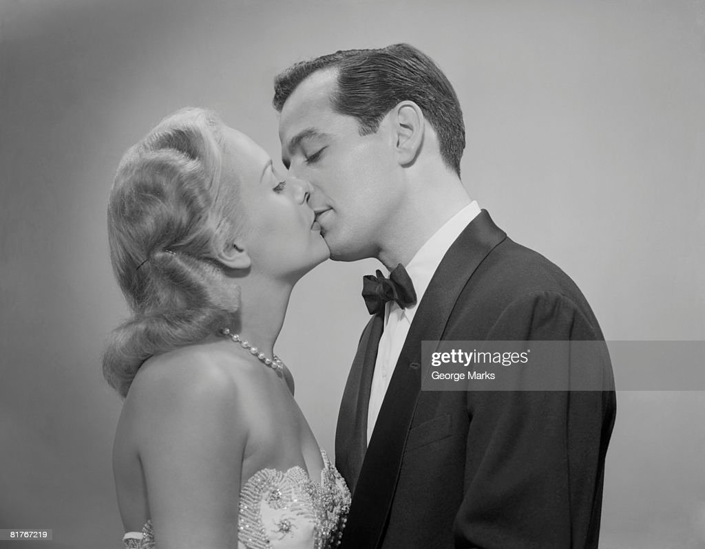 Studio shot of kissing couple in evening wear : Stock Photo