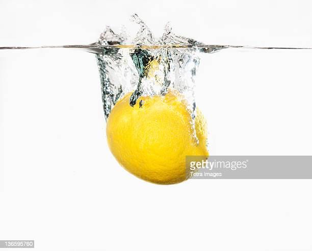 Studio shot of lemon splashing into water