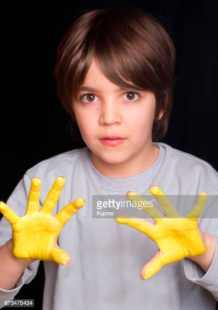 Studio Shot Of Little Boy Age 7 Years, Hands Covering With Yellow Paint