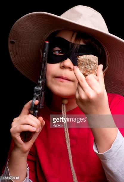 Studio Shot Of Little Boy Age 8 Years Wearing Cowboy Hat Holding Cap Pistol