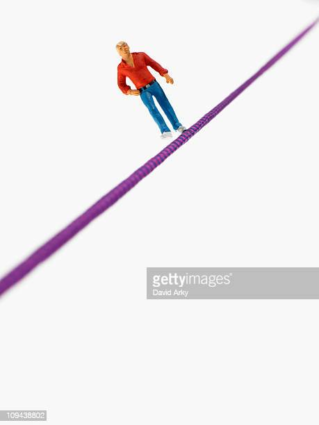 Studio shot of male figurine balancing on tightrope