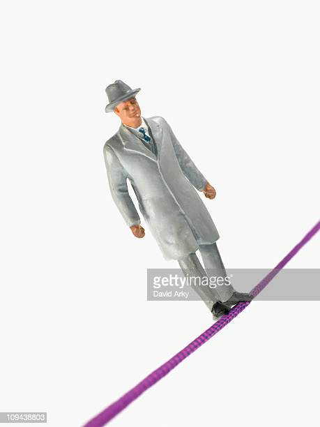 Studio shot of male figurine in suit  balancing on tightrope