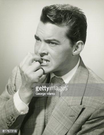 Studio shot of man biting fingers : Stock Photo