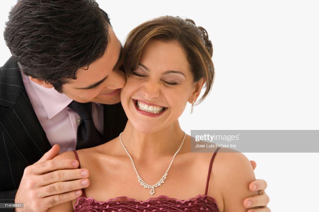 Studio shot of man kissing smiling woman on her cheek : Stock Photo