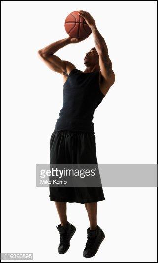 Studio shot of man playing basketball