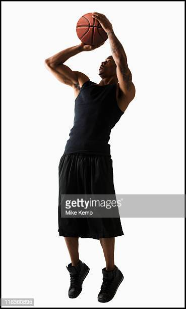 Studio shot of man playing basketball
