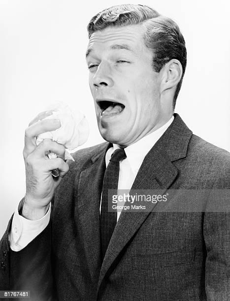 Studio shot of man sneezing