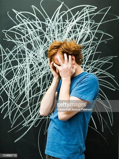 Studio shot of man with chalk scribble on blackboard