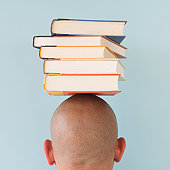 Studio shot of man with stack of books on head