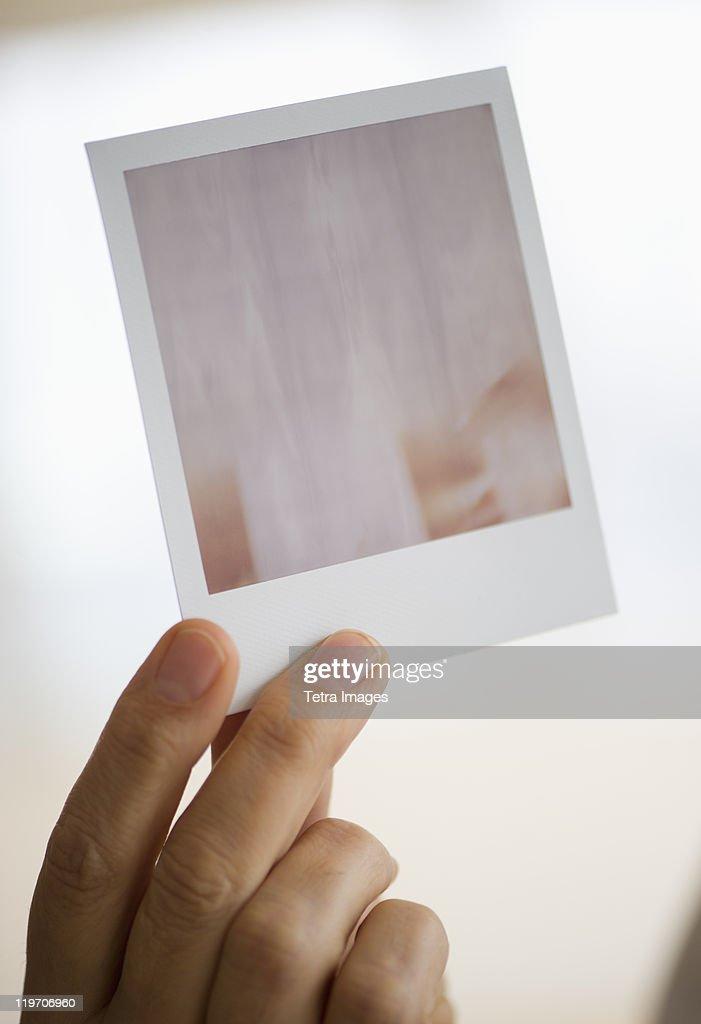 Studio shot of man's hand holding photography
