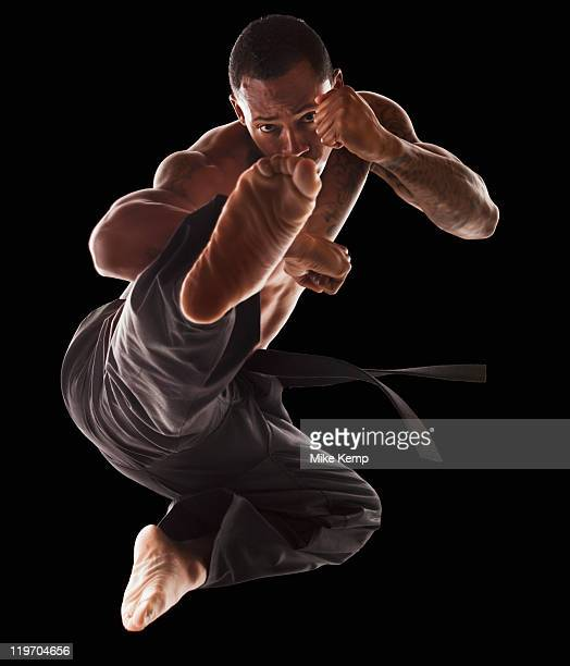 Studio shot of martial arts practitioner in mid-air kick