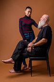 Studio shot of mature bald man with long beard and young beautiful Asian transgender woman against colored background vertical shot