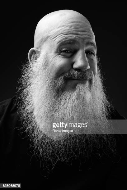 Studio shot of mature bald man with long beard sitting on chair against black background