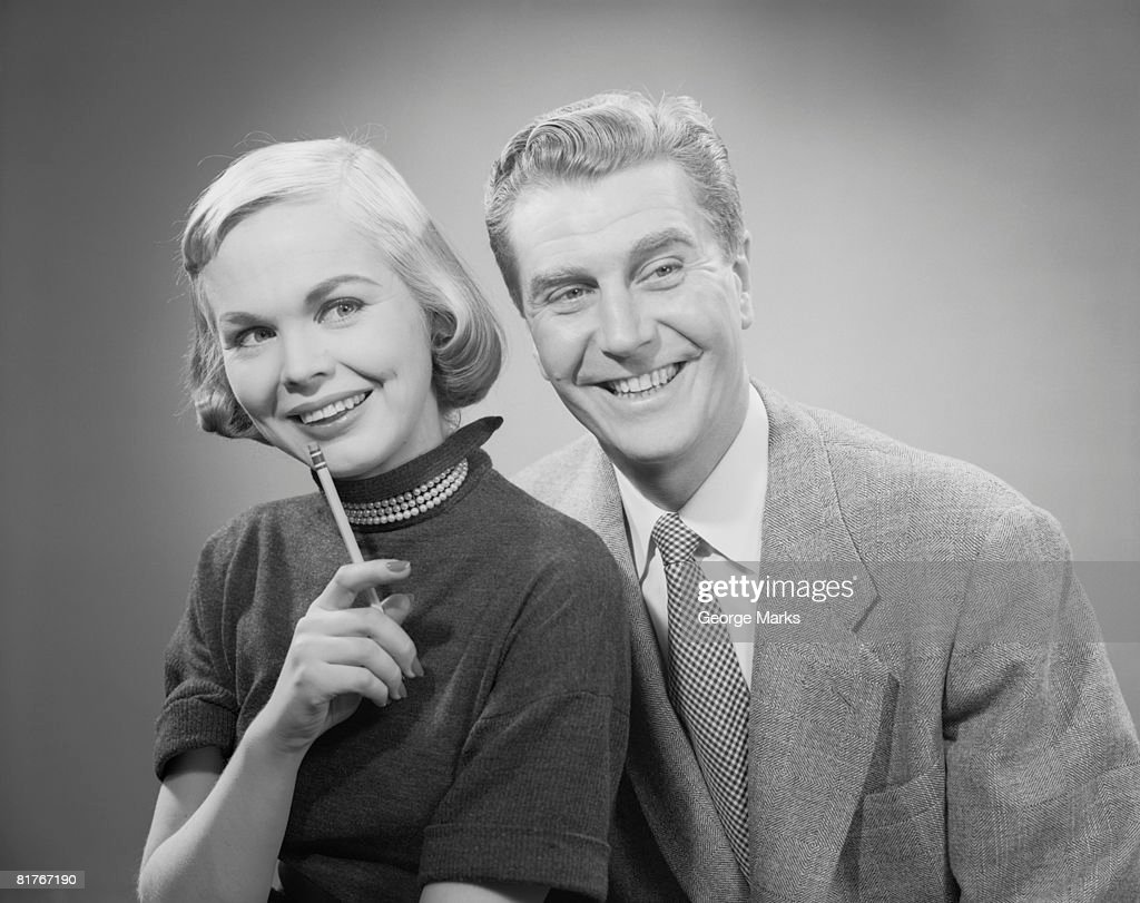 Studio shot of mature couple looking away, woman with pencil : Stock Photo