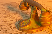 Studio shot of miniature rotary telephone on map of area codes