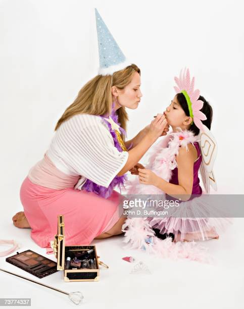 Studio shot of mother and daughter playing dress up