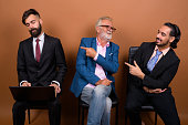 Studio shot of multi ethnic group of three bearded businessmen waiting for an interview together against colored background horizontal shot
