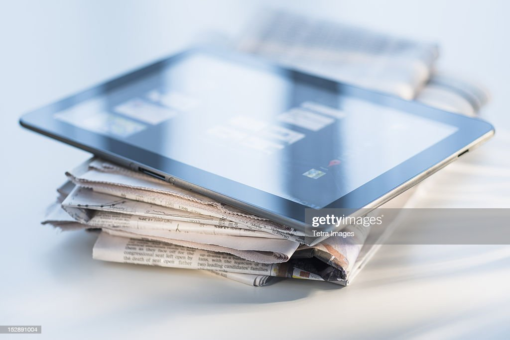 Studio shot of newspaper and tablet PC