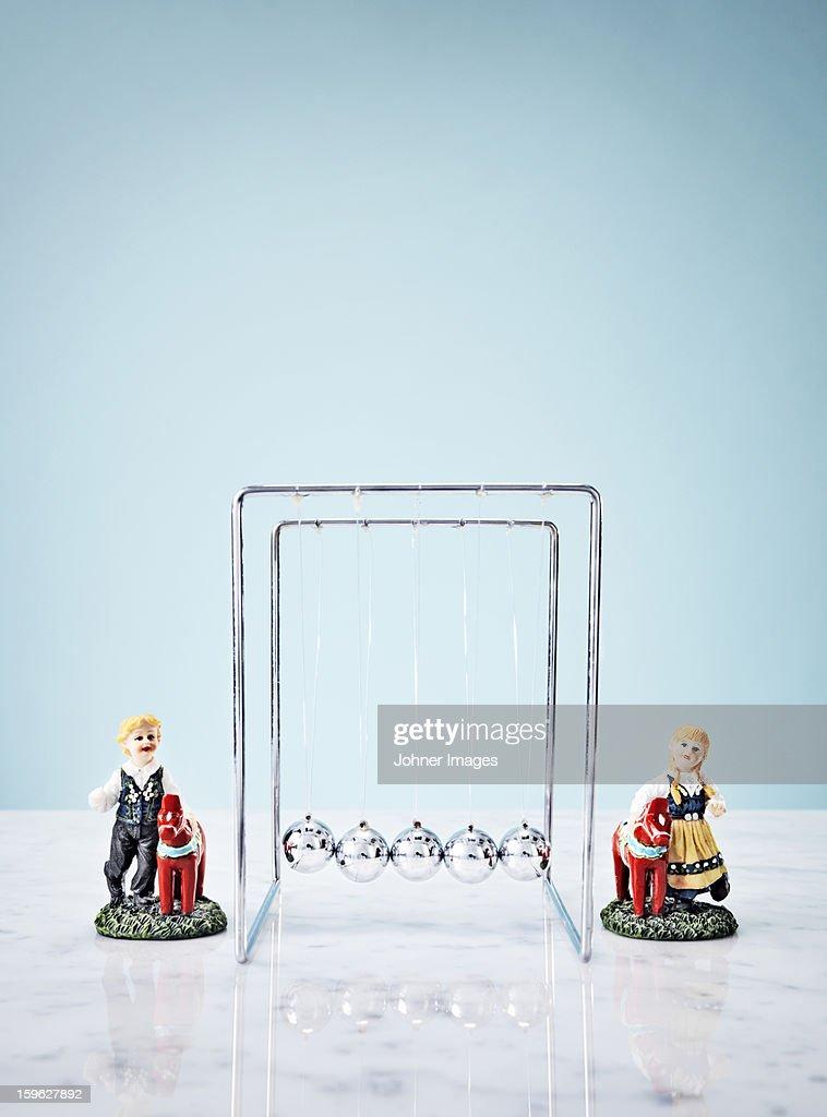 Studio shot of Newtons Cradle and small figurines : Stock Photo