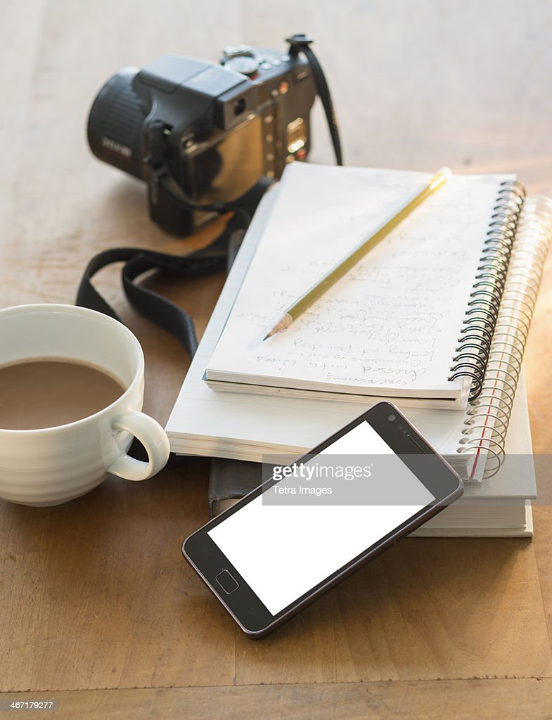 Studio shot of notepads, smartphone, camera and coffee
