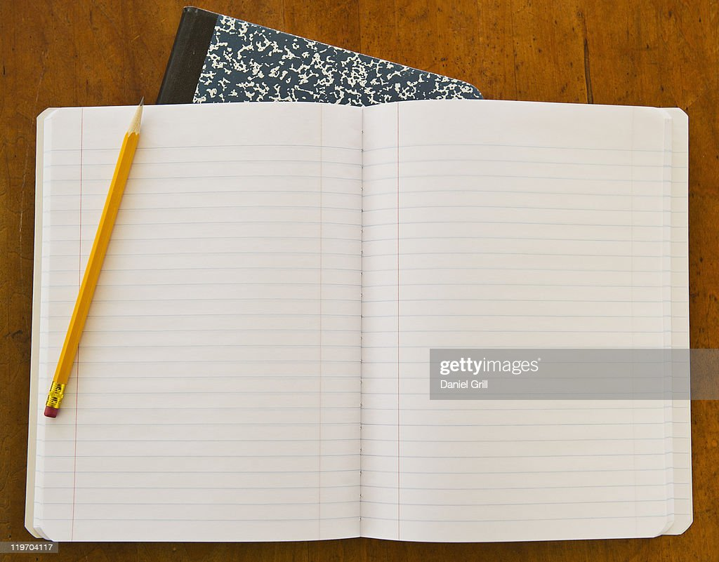 Studio shot of open notebook with yellow pencil