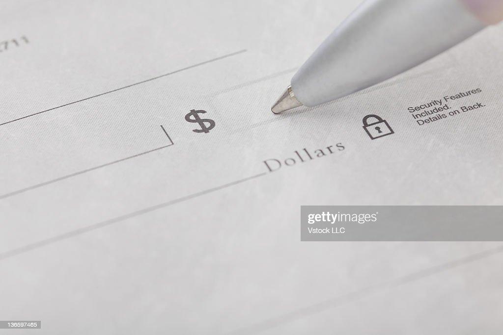 Studio shot of pen writing on receipt