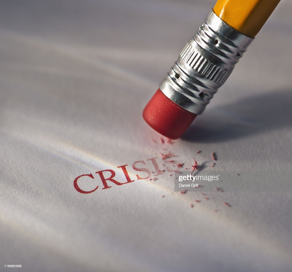 Studio shot of pencil erasing the word crisis from piece of paper