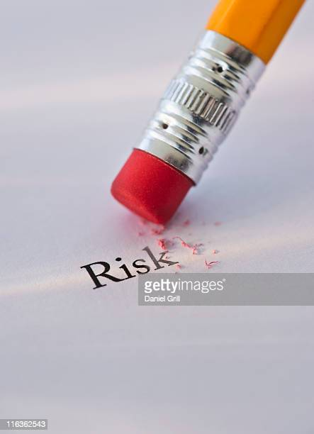 Studio shot of pencil erasing the word risk from piece of paper