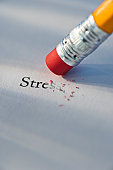Studio shot of pencil erasing the word stress from piece of paper