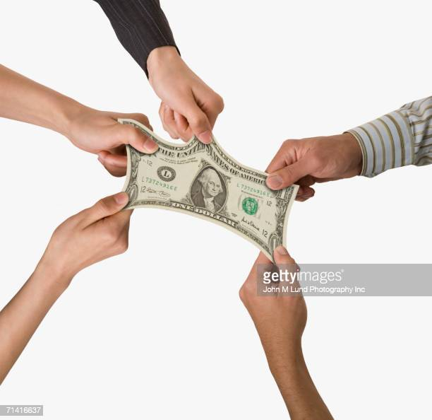 Studio shot of people's hands pulling on dollar bill