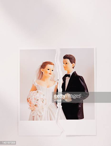 Studio shot of photo of bride and groom figurines torn in half