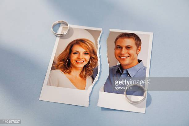 Studio shot of photo of couple torn in half and wedding rings
