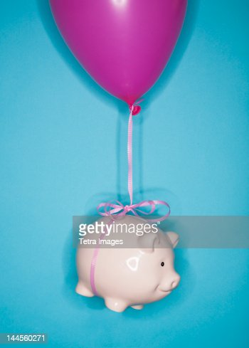 Studio shot of piggy bank lifted by balloon