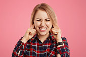 Studio shot of pretty woman clenches teeth and plugs ears with dissatisfaction as hears unpleasant sound or music, has appealing appearance, poses against pink background. Body language concept