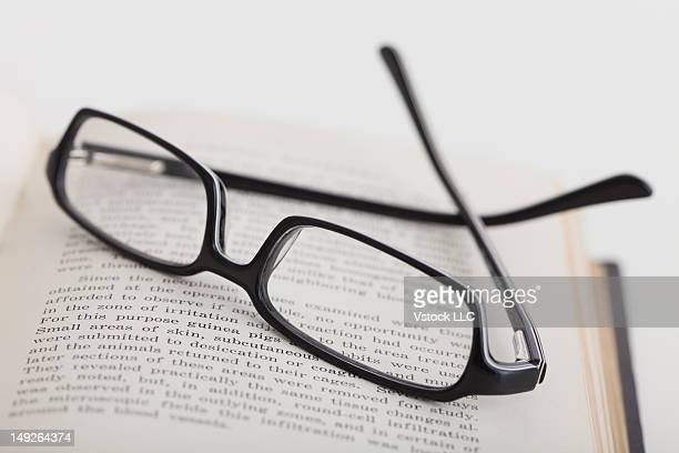 Studio shot of reading glasses on book