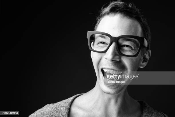 Studio shot of rebellious man wearing eyeglasses against black background