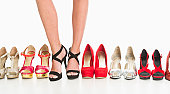 Studio shot of row of shoes, woman wearing one of them