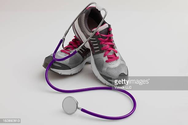 Studio shot of running shoes and stethoscope