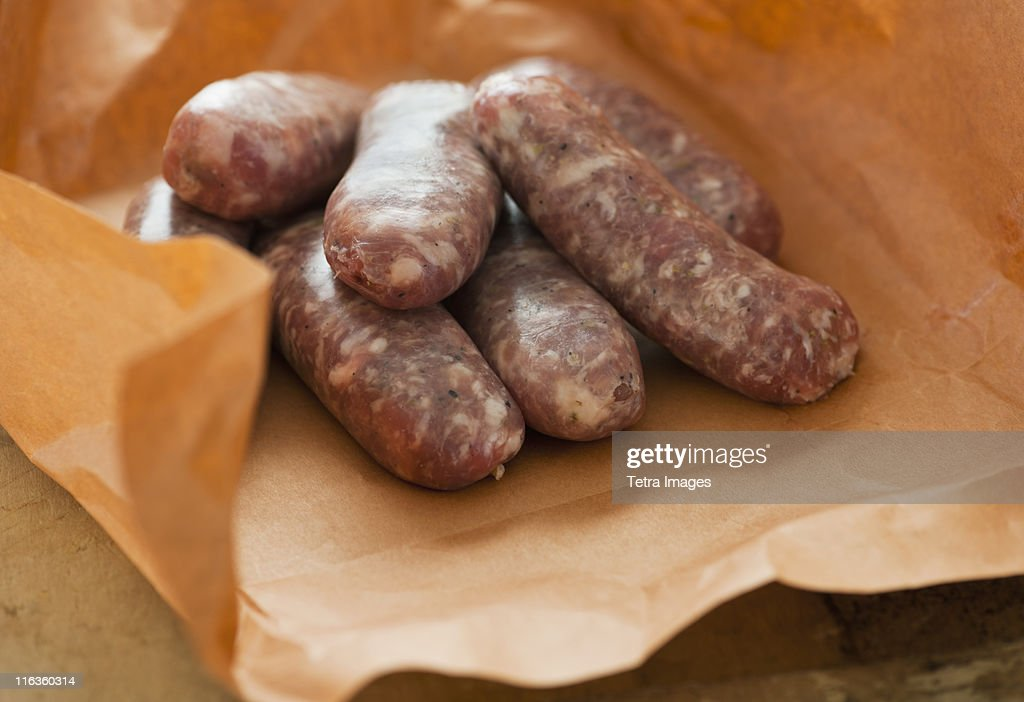 Studio shot of sausage wrapped in brown paper : Stock Photo