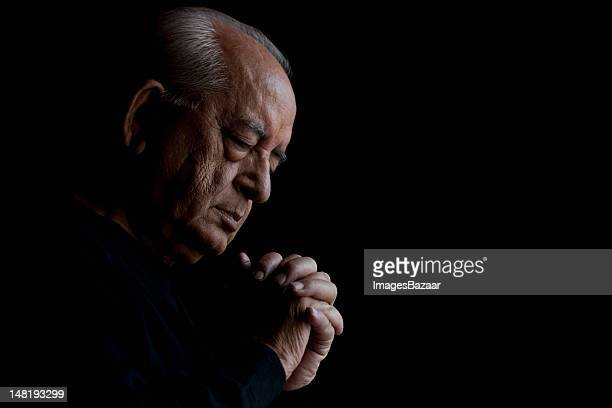 Studio shot of senior man praying