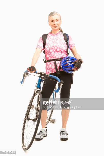 Studio shot of senior woman with bicycle and helmet