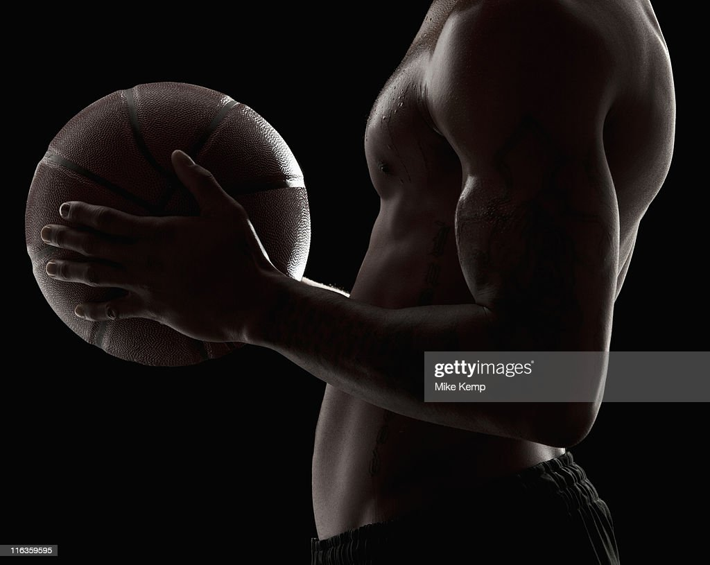 Studio shot of shirtless man holding basketball, mid section : Stock Photo