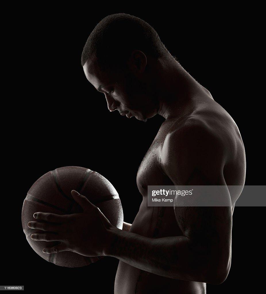 Studio shot of shirtless man holding basketball : Stock Photo